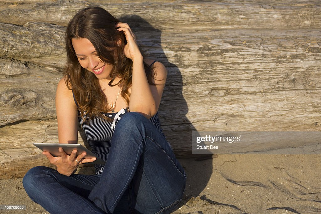 Student at the beach using a tablet : Stock Photo