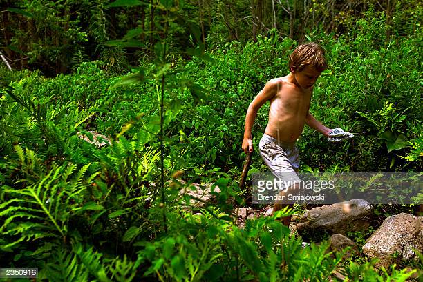 A student at the Center for Attention and Related Disorders camp makes his way through the forest after making plaster casts of animal tracks at the...