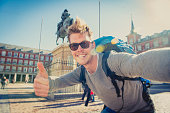 young attractive student backpacker tourist taking selfie photo with stick and mobile phone outdoors enjoying holidays travel destination in tourism and exploring concept
