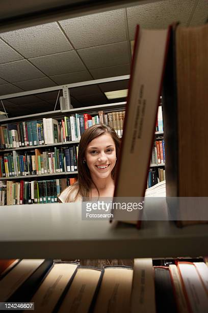 Student behind bookcase in library (portrait)