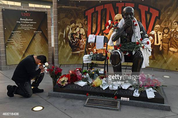 UNLV student Caesar Castillo kneels by a statue of Jerry Tarkanian outside the Thomas Mack Center at UNLV during a gathering of fans for the Naismith...