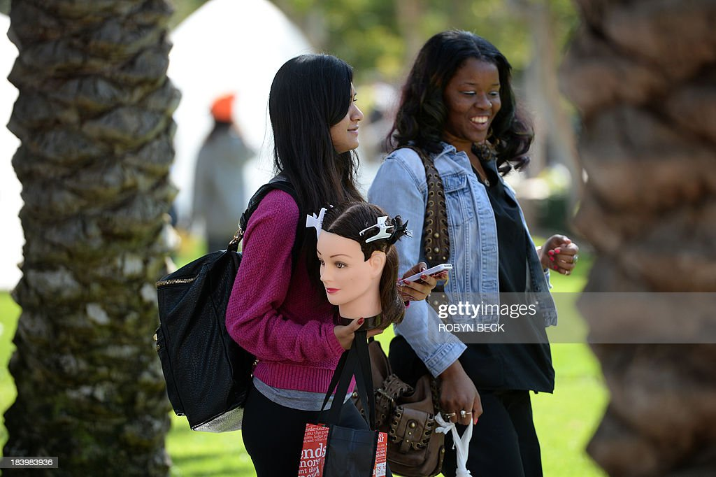 A student carries a cosmetology training mannequin head and her cell phone as she walks with a friend on the campus of Santa Monica City College in Santa Monica, California October 10, 2013. AFP PHOTO / Robyn Beck