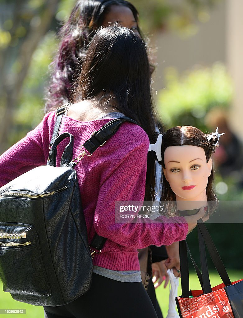 A student carries a cosmetology training mannequin head on the campus of Santa Monica City College in Santa Monica, California October 10, 2013. AFP PHOTO / Robyn Beck