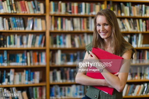 Student carrying binder in library