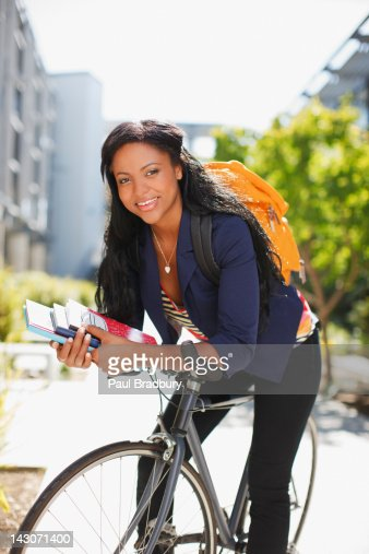 Student carrying books on bicycle