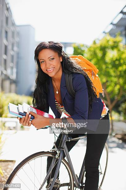 Studente che trasportano i libri in bicicletta