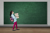 Picture of cute student carrying pile of books while walking in the classroom
