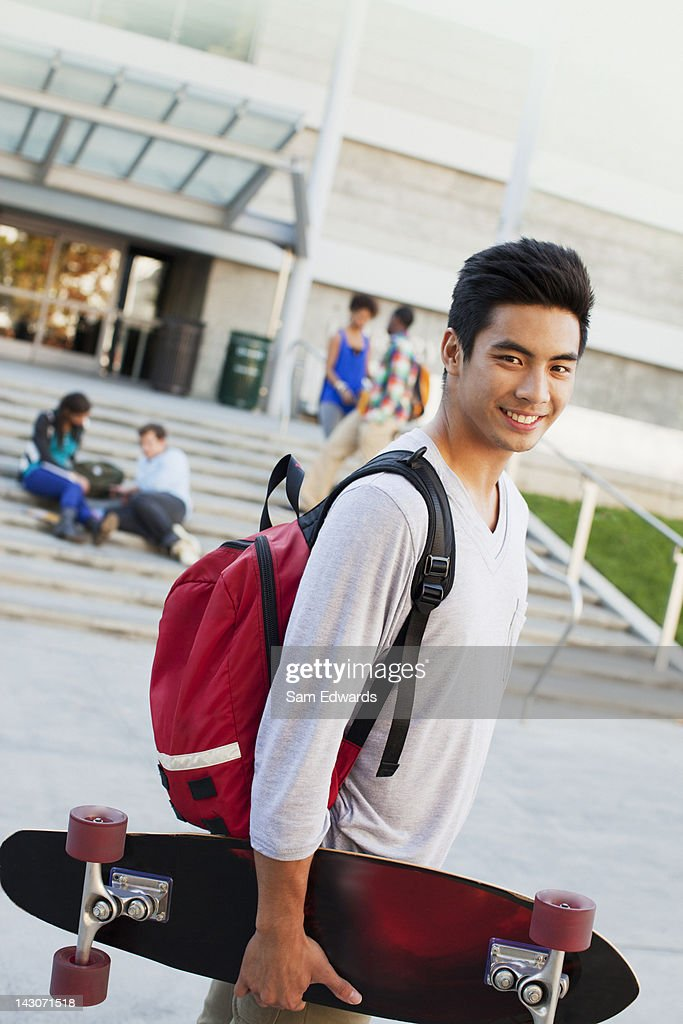 Student carrying skateboard outdoors : Stock Photo