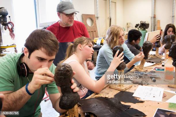 Student carving wax figures in class