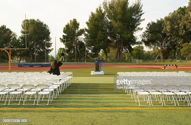 Student celebrates graduation among empty seats, rear view