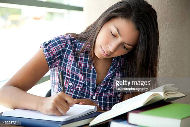 Student concentrating on writing in book with other books