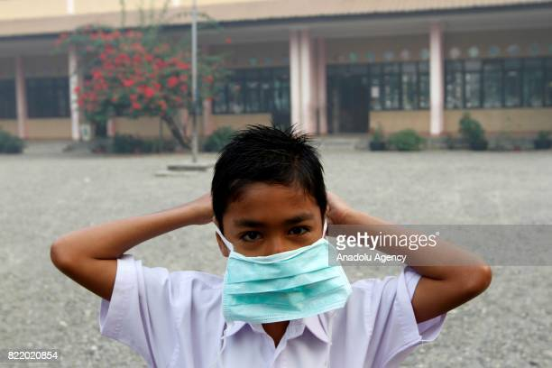 A student covers his face with a mask due to smoke from peat forest fire in Aceh Indonesia on July 25 2017 The number of hotspots in Indonesia...