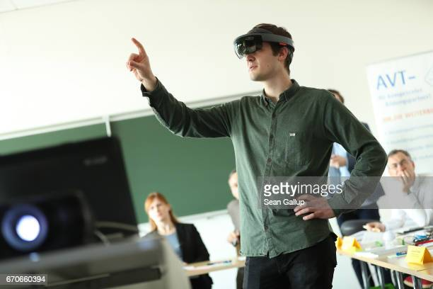 A student demonstrates the use of Microsoft mixed reality goggles which combine a virtual reality display with regular view during a visit by German...