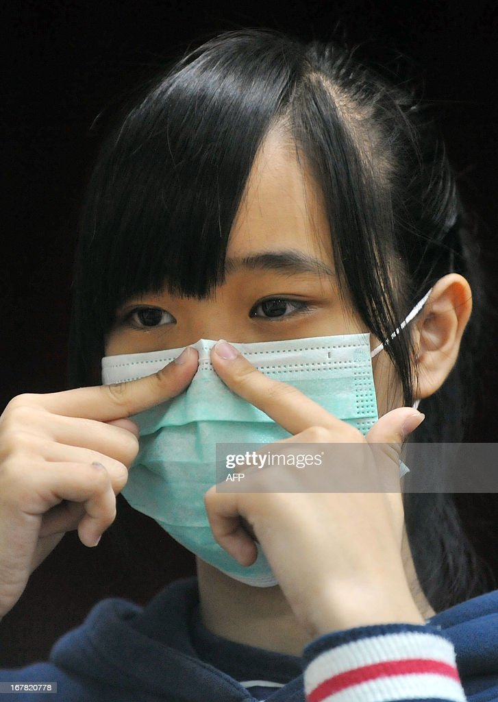 A student demonstrates wearing a mask correctly in a junior high school in Taipei on May 1, 2013. The deadly H7N9 bird flu strain claimed a new victim when a hospital patient died in China, state media reported, bringing the death toll from the recently identified virus to 24. AFP PHOTO / Mandy CHENG