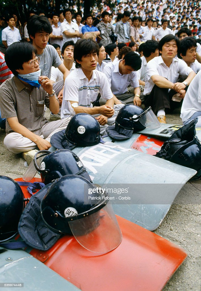 Student demonstrators sit with police riot gear during a protest in Seoul. Students and other demonstrators who joined them all over South Korea protested the political and economic situation and eventually brought the regime of President Chun Doo Hwan to an end. In October 1987, the National Assembly ratified a new constitution, which provided for direct presidential elections.