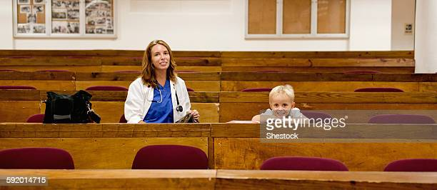Student doctor and son sitting in college classroom