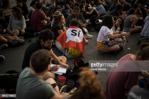 A student draped in a flag that it reads 'Si' Yes in Catalan attends to a video conference of Julian Assange outside the University of Barcelona on...