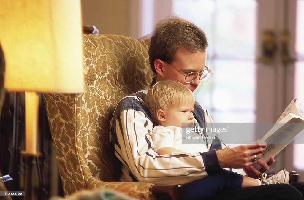Student father w/son reading in chair in dorm : Stock Photo