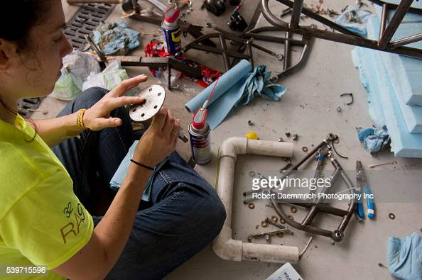 A student from Principia College in Elsah Illinois cleans an axle damaged in an overnight electrical fire that disabled several solar cars during...