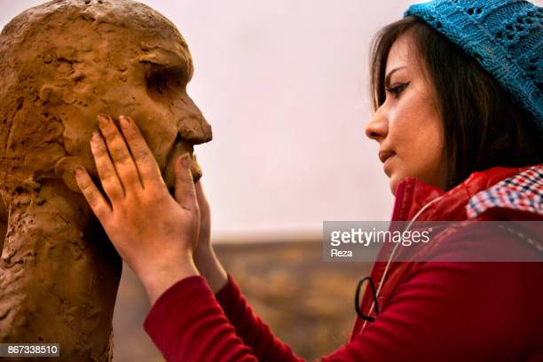 A student from the Academy of Fine Arts is sculpting a bust inside her class in Salahaddin UniversityErbil The university attract students thanks to...