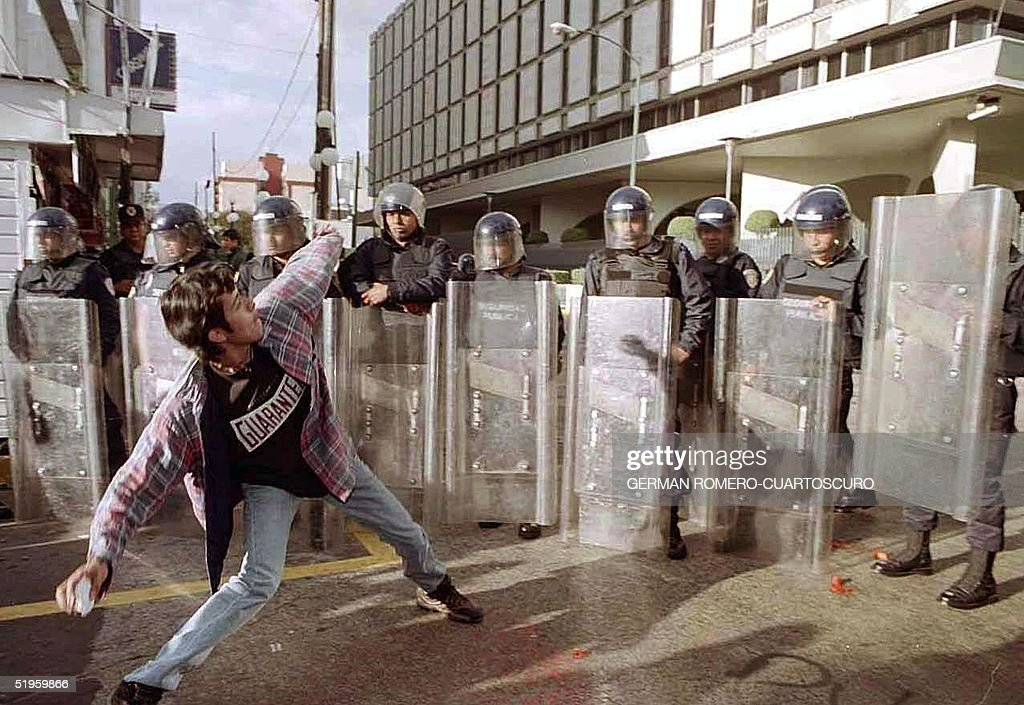 A student from the Autnonous University of Mexico City faces antiriot police in front of the US Embassy 11 December 1999 in the Mexican capital...