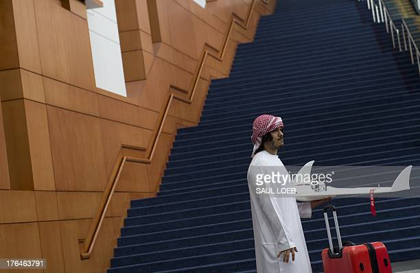 A student from the United Arab Emirates carries a drone during the Unmanned Systems 2013 exhibition and symposium hosted by The Association for...