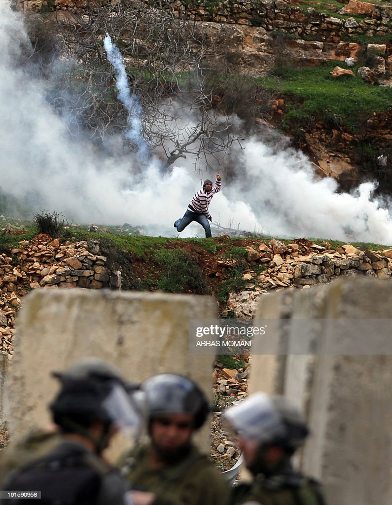 A student from the University of Birzeit hurls a smoke grenade towards Israeli security forces outside Israel's Ofer military prison, near the West Bank city of Ramallah, on February 12, 2013, following a demonstration in support of Palestinian prisoners on hunger strike in Israeli jails.