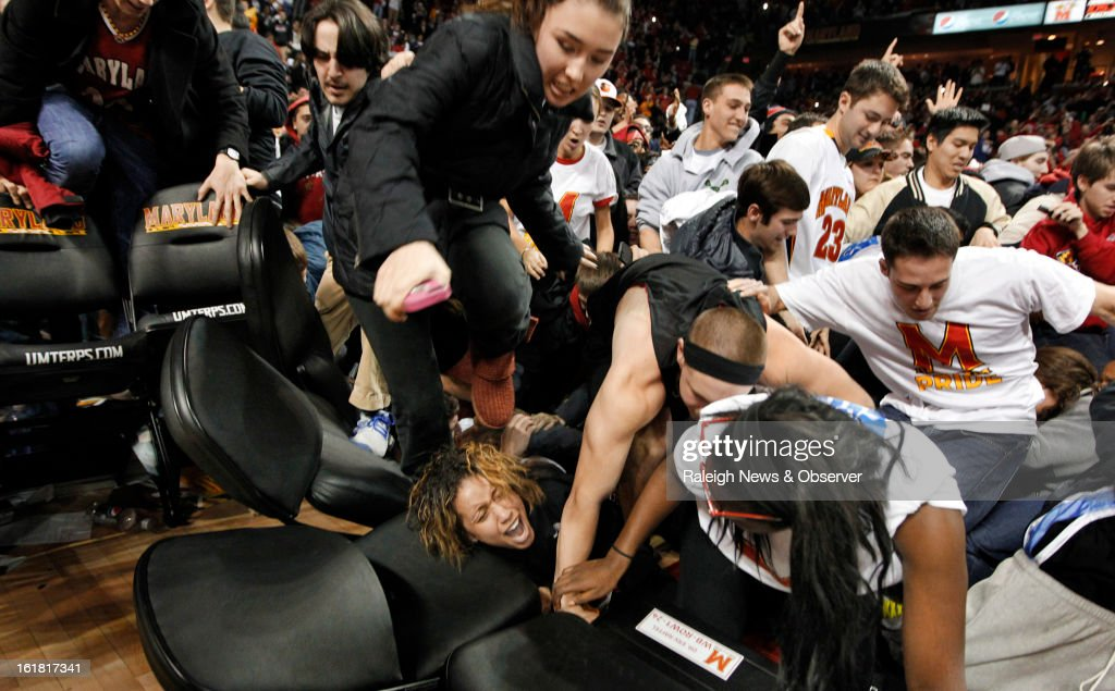 A student gets trapped under chairs as a tidal wave of Maryland fans rush the court, after Maryland upset Duke, 83-81, at the Comcast Center in College Park, Maryland, Saturday, February 16, 2013.