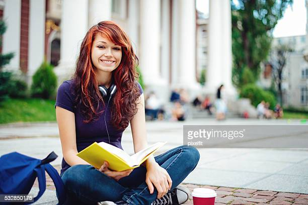 Student girl reading book in front of Univercity