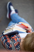 Student girl closing tight a heap of textbooks and notebooks. Back to school concept photo, view over the head