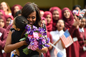 A student gives flowers to embraces and welcomes with other young students US First Lady Michelle Obama in the courtyard before an event as part of...