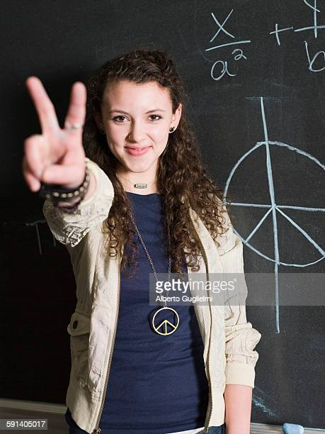 Student giving peace sign at chalkboard in classroom
