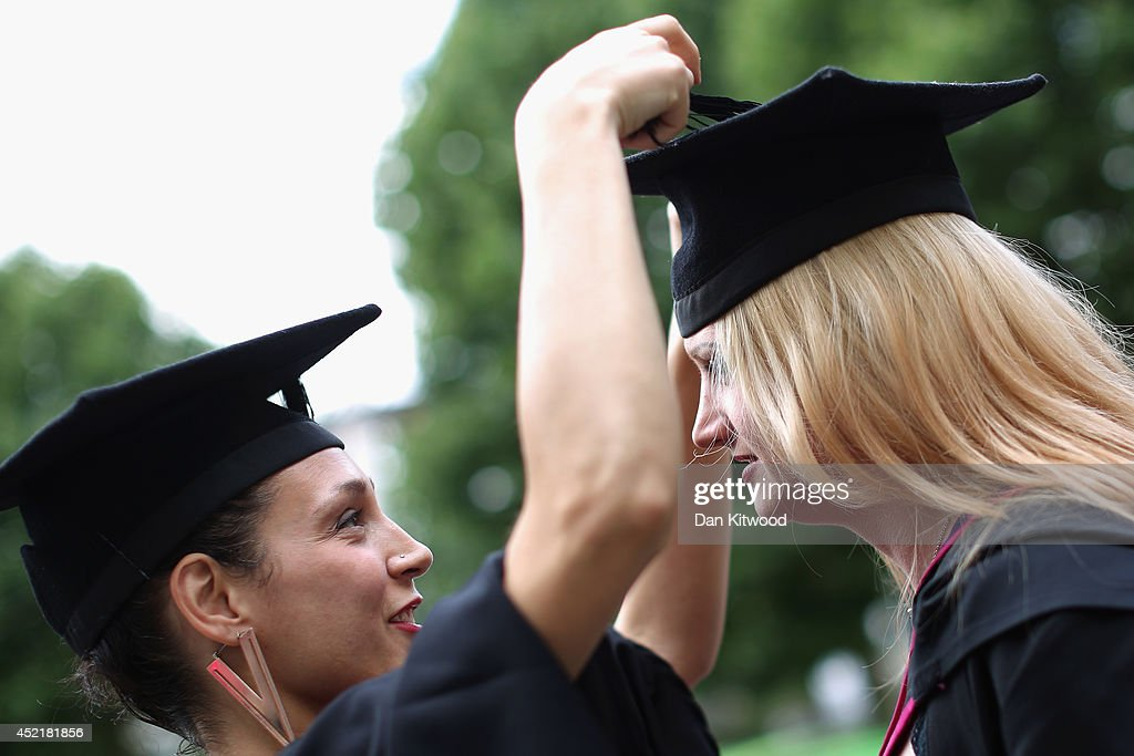 A student has her cap adjusted by her friend ahead of her graduation ceremony at the Royal Festival Hall on July 15, 2014 in London, England. Students of the London College of Fashion, Management and Science and Media and Communication attended their graduation ceremony at the Royal Festival Hall today.