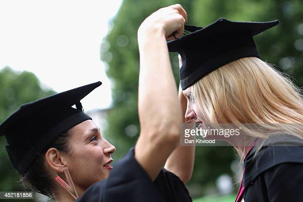 A student has her cap adjusted by her friend ahead of her graduation ceremony at the Royal Festival Hall on July 15 2014 in London England Students...