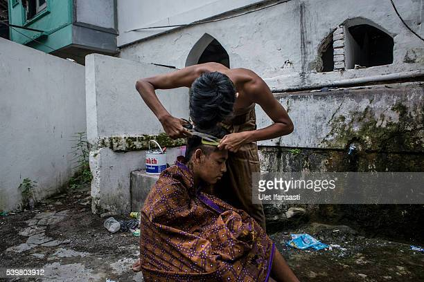 A student helps cut his friends hair at the islamic boarding school Lirboyo during the holy month of Ramadan on June 9 2016 in Kediri East Java...