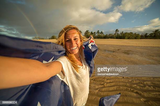Student holding Australian flag on beach