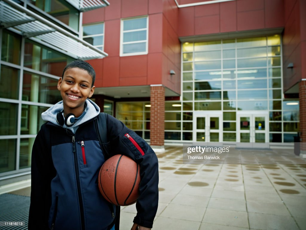 Student holding basketball outside of school