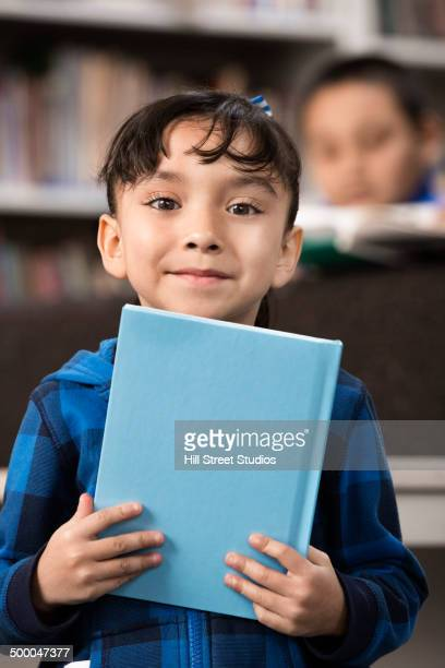 Student holding book in library