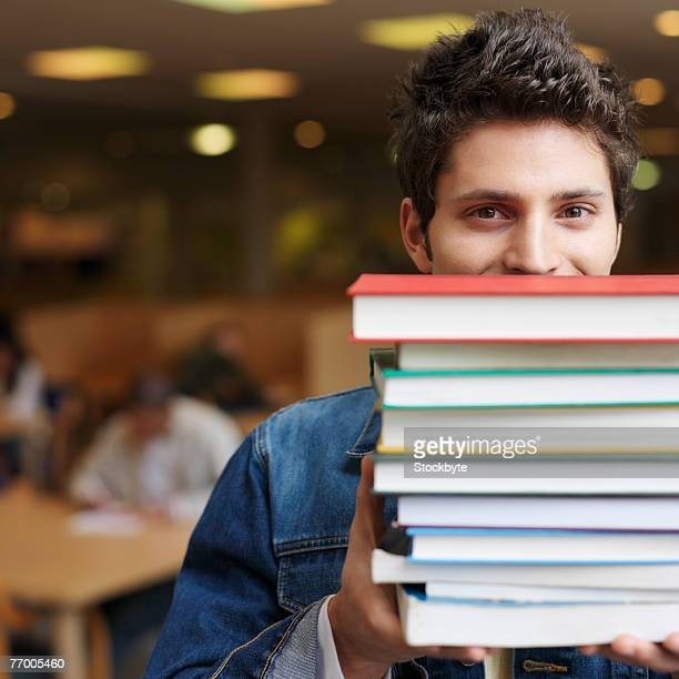 Student holding books in front of face in library, portrait