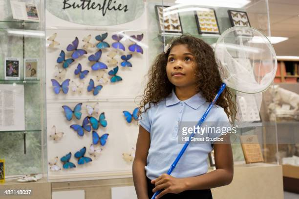 Student holding butterfly net in museum