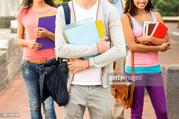 Student Holding Files With Friends Standing In Background
