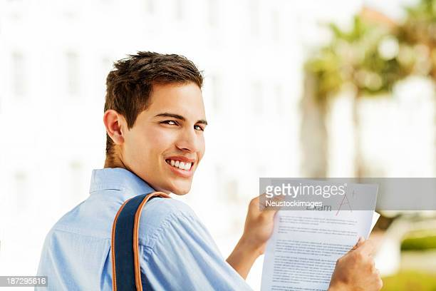 Student Holding Test Result With A+ Grade On Campus