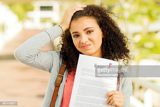 Student Holding Test Result With F Grade On University Sidewalk