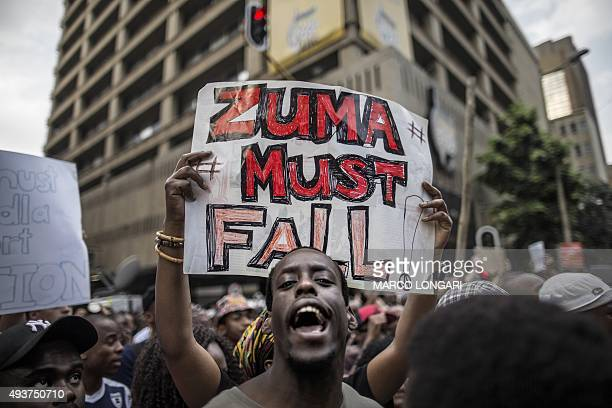 A student holds a placard reading 'A placard with 'Zuma must fall' outside the Luthuli House the ANC headquarters on October 22 in Johannesburg...