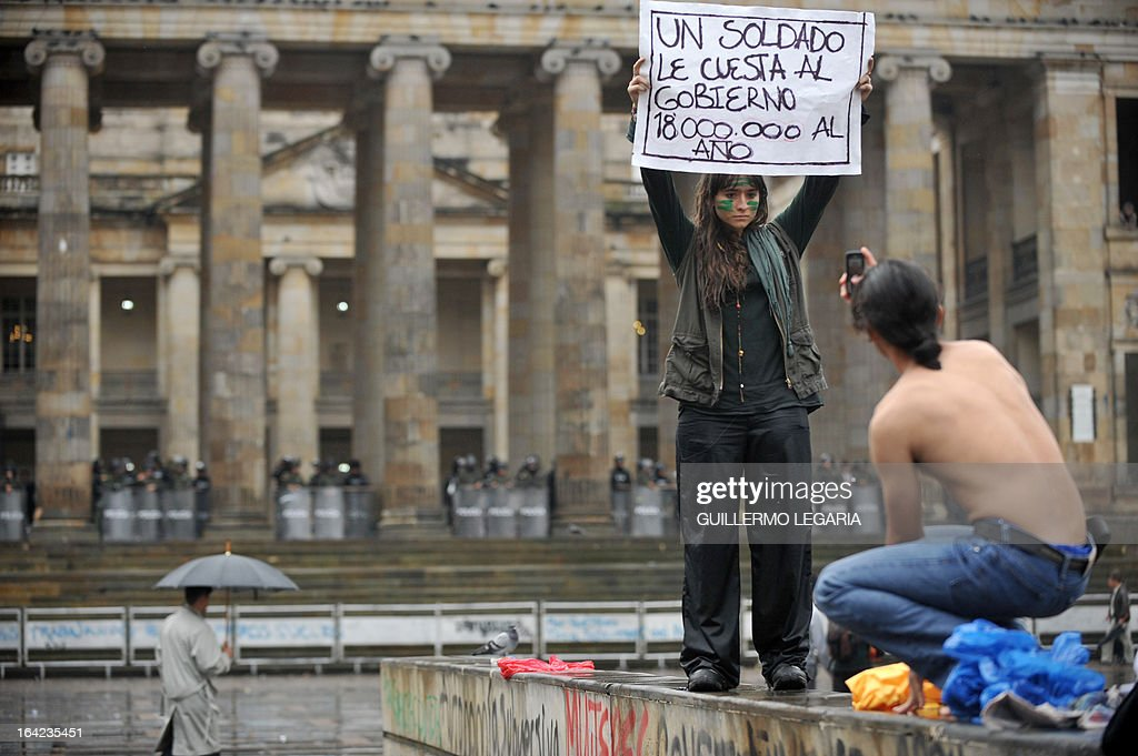 A student holds a placard that reads 'A soldier costs to the government 18 million a year' during a protest in Bogota, Colombia on March 21, 2013, demanding a better and free education and an alternative university reform. AFP PHOTO/Guillermo Legaria