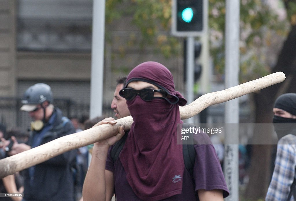 A student holds a stick during clashes with riot police during a protest to demand Chilean President Sebastian Pinera's government an intensive educational reform and to break with other legacies of the dictatorship of Augusto Pinochet (1973-1990), in Santiago, on September 5, 2013. AFP PHOTO/Claudio SANTANA