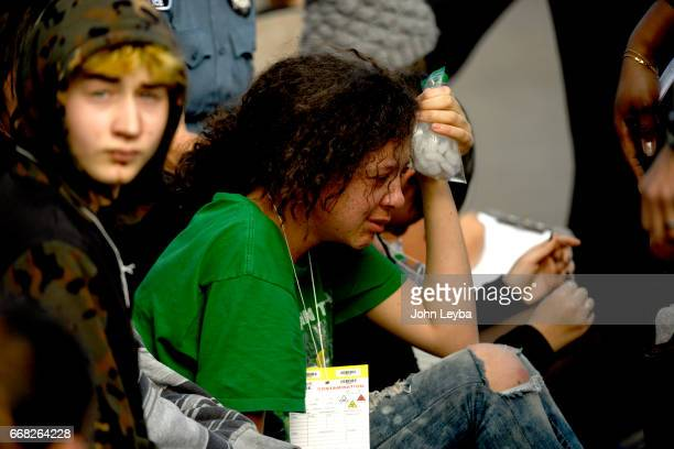 A student holds an ice pack on her head as paramedics work on kids at 39th Tejon after their bus they were in was hit by a Grand Cherokee on April 13...
