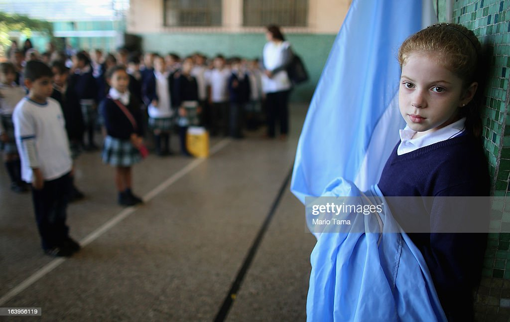 A student holds the Argentinian flag in the Instituto Nuestra Senora del Huerto Catholic school, founded in 1872, which Pope Francis visited, on March 18, 2013 in Buenos Aires, Argentina. Francis was the archbishop of Buenos Aires and is the first Pope to hail from South America. Francis will be officially installed as Pope tomorrow at Saint Peter's Square.