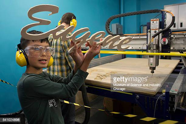 A student holds up the result of a computeraided design and fabrication project the name 'Eugene' cut in wood by a 'ShopBot' during a summer school...