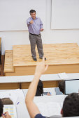Student in a lecture hall putting hand up and lecturer pointing at him